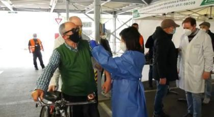 Taranto – Applausi per anziano che arriva in bici al drive-through per vaccinarsi